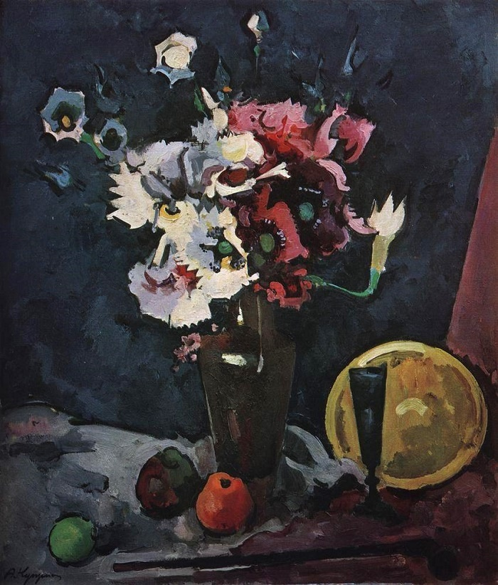 White and pink artificial flowers against the black background, with a yellow bowl and a blue goblet. 1929