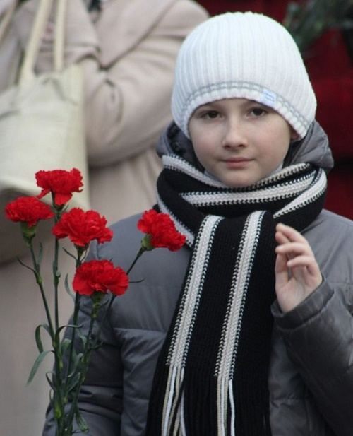 A girl with carnation flowers, usual attribute on Great October revolution day and demonstration of 7 November